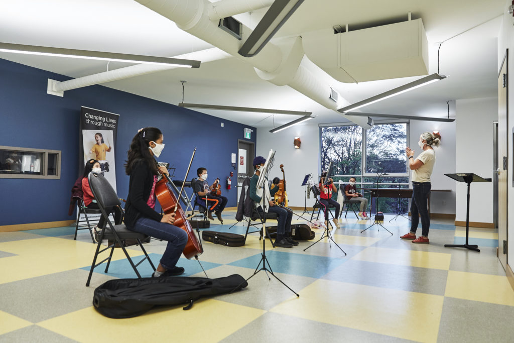 Children playing cello and violins wearing masks.