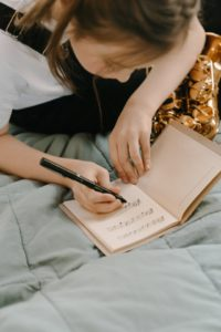 Girl writing in notebook on bed