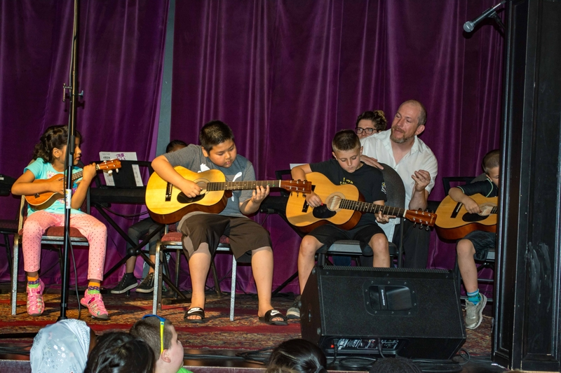 Students playing guitar on stage with adult instructor